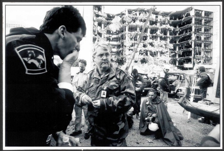 Second Place News 'Communion' by Tech. Sgt. Marvin Krause, U.S. Air Force. U.S. Army Chaplain Lt. Col. Roberson gives communion to search and rescue workers across the street from the Alfred P. Murrah Federal Building, site of the worst terrorist act in American history. A fertilizer bomb exploded causing catastrophic damage to the building and surrounding area and killing 169 and injuring over 500 innocent men, women and children.