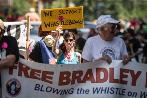 Marchers in the 2013 Twin Cities Pride parade carry signs announcing support for whistleblowers and Chelsea (Bradley) Manning, Minneapolis, Minnesota.